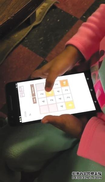 """一名儿童正在安卓系统的智能手机上玩""""2048""""游戏,进行iCare软件的实验。受访者供图"""